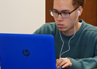 Student with headphones plugged into a laptop